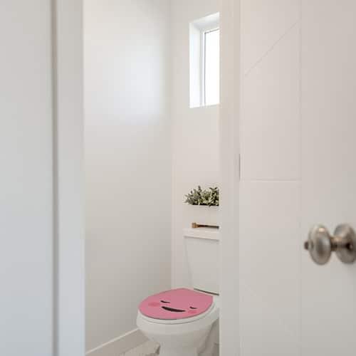 Sticker rose touchant collé sur des WC