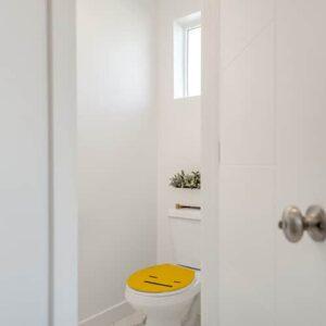 Sticker jaune blasé collé sur des WC