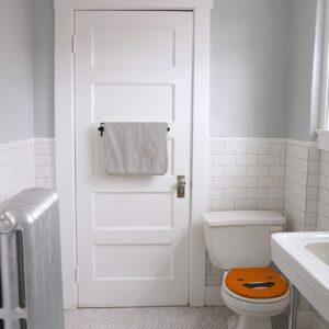 Sticker adhésif Smiley heureux orange sur des WC