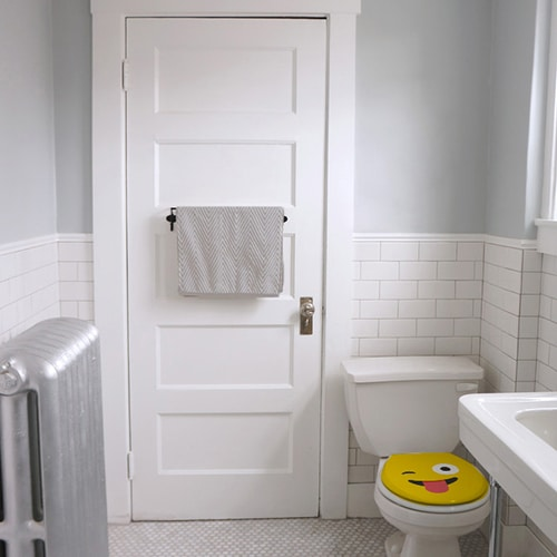 Sticker Smiley jaune qui tire la langue collé sur des WC