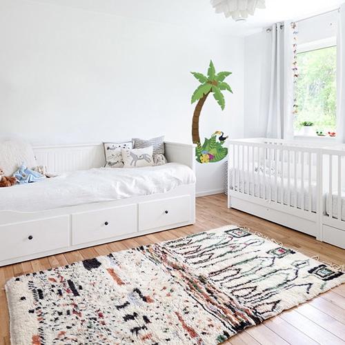 sticker mural palmier pour enfant mis en ambiance dans une chambre pour bébé