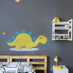Adhésif mural pour enfant Dinosaure Jaune et Bleu sur une flaque d'eau, mis en ambiance sur un mur gris foncé