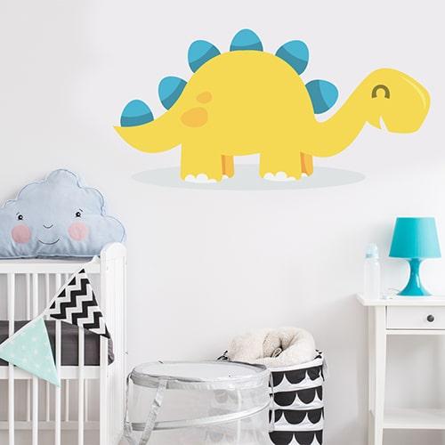 autocollant mural pour enfant Dinosaure Jaune et Bleu sur une flaque d'eau, mis en ambiance sur un mur blanc d'une chambre pour bébé