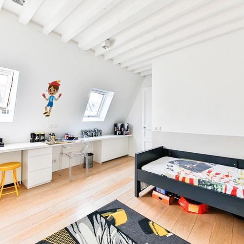 adhésif mural Pinocchio pour enfants mis en ambiance dans une chambre aux murs blancs
