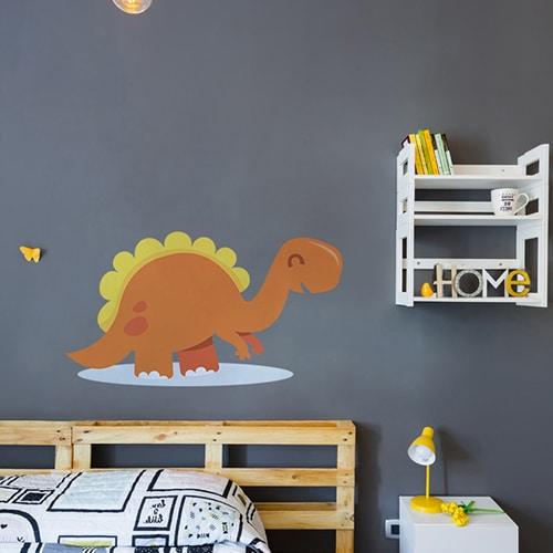 Sticker mural Dinosaure Orange et Jaune pour enfants mis en ambiance sur mur gris foncé