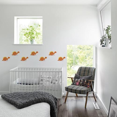 plusieurs Stickers muraux Dinosaures Orange et Jaune pour enfants mis en ambiance dans la décoration d'une chambre pour bébé