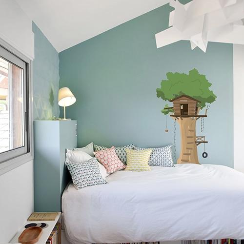 sticker mural pour enfant cabane en haut d'un arbre mis en ambiance sur un mur couleur claire