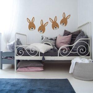 quatre adhésifs muraux petits lapins pour enfants mis en ambiance sur un mur blanc