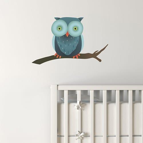 sticker pour enfant hibou sur une branche mis en ambiance dans une chambre pour bébé aux murs blancs