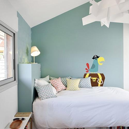 Sticker pour enfant perroquet vert sur son trésor mis en ambiance sur un mur vert clair