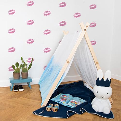 Stickers baisers roses sur mur blanc derrière une mini tente pour enfants