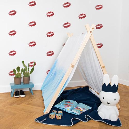 Stickers baisers rouges sur mur blanc derrière une mini tente pour enfants