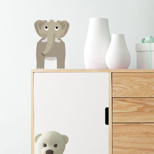 Sticker Éléphant enfants mis en ambiance sur mur blanc juste au dessus d'un meuble