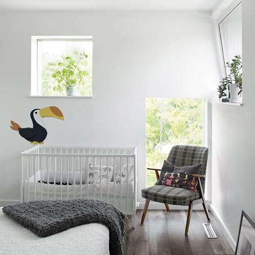 sticker toucan mis en ambiance sur le mur blanc d'une chambre de bébé derrière un berceau