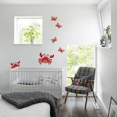 Stickers Crabes rouges enfants disposés sur un mur blanc d'une chambre pour bébé derrière le berceau