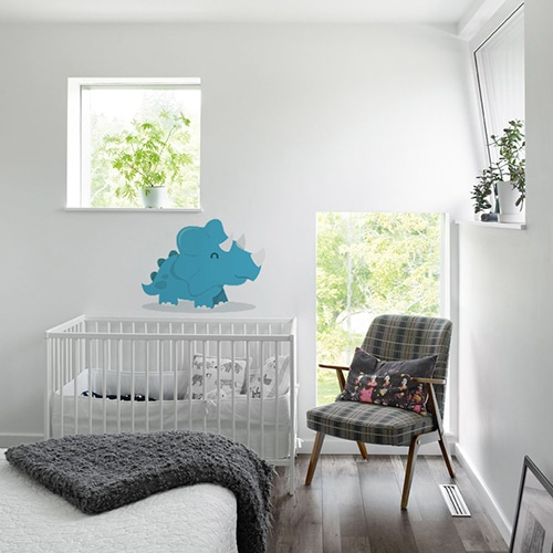 sticker dinosaure bleu avec ombre sur mur blanc au dessus d'un berceau pour bébé