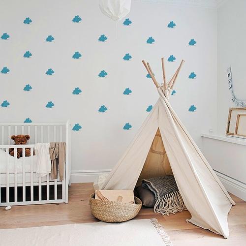 Stickers Dinosaures Bleus avec ombres pour enfants parsemés sur le mur clair d'une chambre pour bébé
