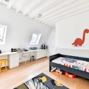 Sticker dinosaure rouge enfant avec ombre sur mur blanc dans une chambre pour enfants