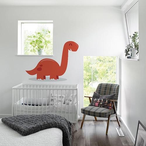 Sticker dinosaure rouge enfant avec ombre sur mur blanc au dessus d'un berceau