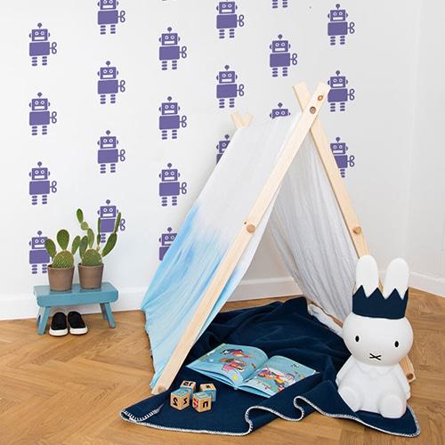 Mosaïque de stickers violets mis en ambiance sur un mur blanc d'une chambre pour enfant