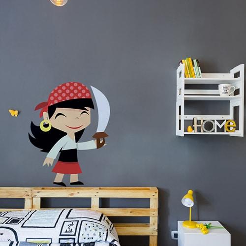 Sticker petite fille pirate souriante avec une épée mis en ambiance sur mur gris foncé