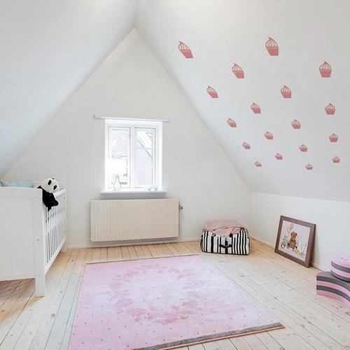 mosaïque de stickers cupcakes roses pour enfant mis en ambiance sur mur blanc d'une chambre d'enfants