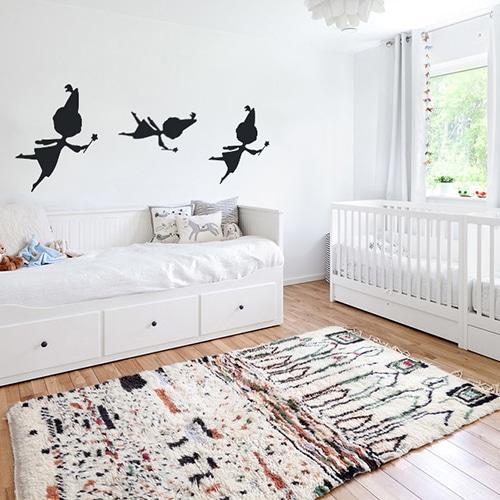 trois stickers muraux fées noires mis en ambiance sur un mur blanc d'une chambre de bébé
