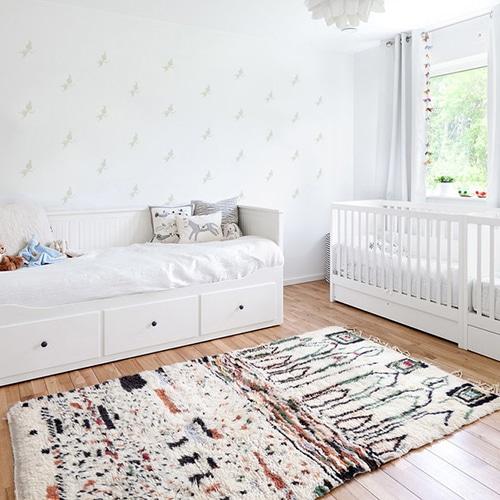 Mosaïque de stickers fées beiges sur mur blanc dans une chambre de bébé