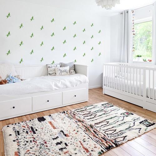 Mosaïque de stickers fées vertes sur mur blanc dans une chambre de bébé