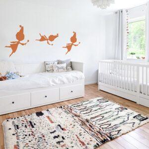trois stickers muraux fées oranges mis en ambiance sur un mur blanc d'une chambre de bébé