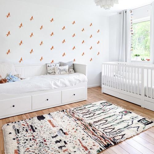 Mosaïque de stickers fées oranges sur mur blanc dans une chambre de bébé