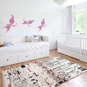 trois stickers muraux fées roses mis en ambiance sur un mur blanc d'une chambre de bébé