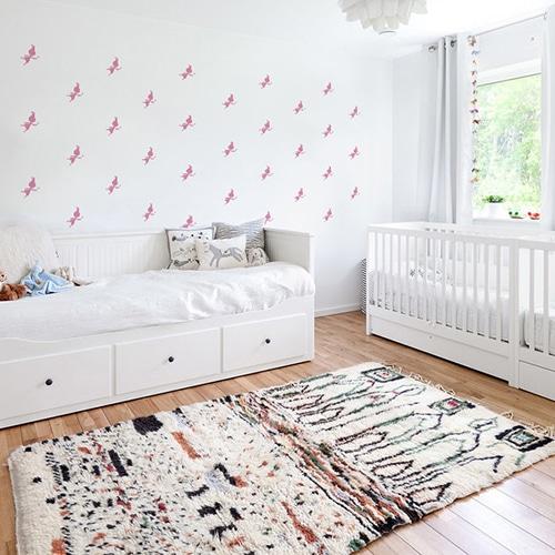 Mosaïque de stickers fées roses sur mur blanc dans une chambre de bébé