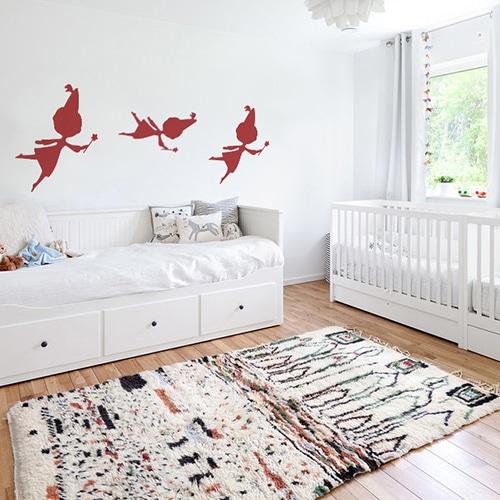 trois stickers muraux fées rouges mis en ambiance sur un mur blanc d'une chambre de bébé