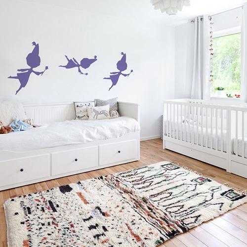 trois stickers muraux fées violettes mis en ambiance sur un mur blanc d'une chambre de bébé