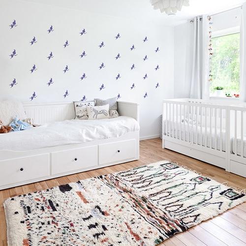 Mosaïque de stickers fées violettes sur mur blanc dans une chambre de bébé
