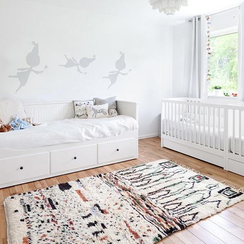trois stickers muraux fée grise mis en ambiance sur un mur blanc d'une chambre de bébé