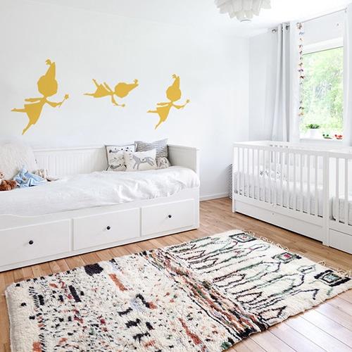 trois stickers muraux fées jaunes mis en ambiance sur un mur blanc d'une chambre de bébé