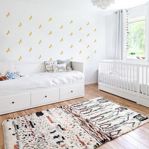Mosaïque de stickers fées jaunes sur mur blanc dans une chambre de bébé