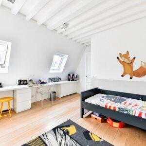 Adhésif mural renard heureux mis en ambiance sur le mur blanc d'une chambre pour enfants