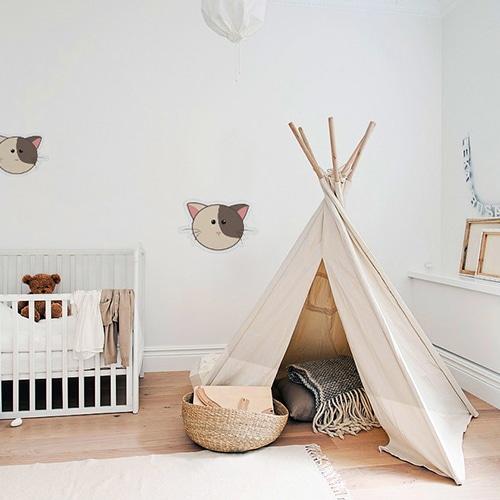 Stickers muraux pour enfants tête de chat bicolore mis en ambiance dans une chambre pour bébé
