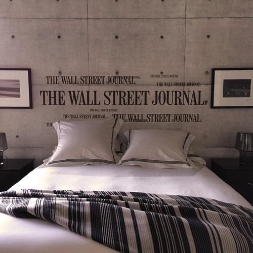 Sticker Wall Street Journal pour tête de lit sur mur gris au-dessus d'un lit blanc et noir