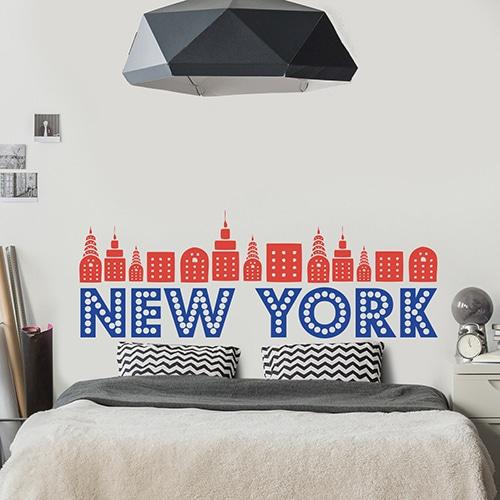 Sticker New-York Rouge et Bleu pour tête de lit sur mur blanc au-dessus d'un lit blanc et gris