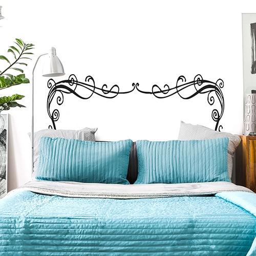 Sticker Rubans Baroques pour tête de lit sur mur blanc au-dessus d'un lit bleu