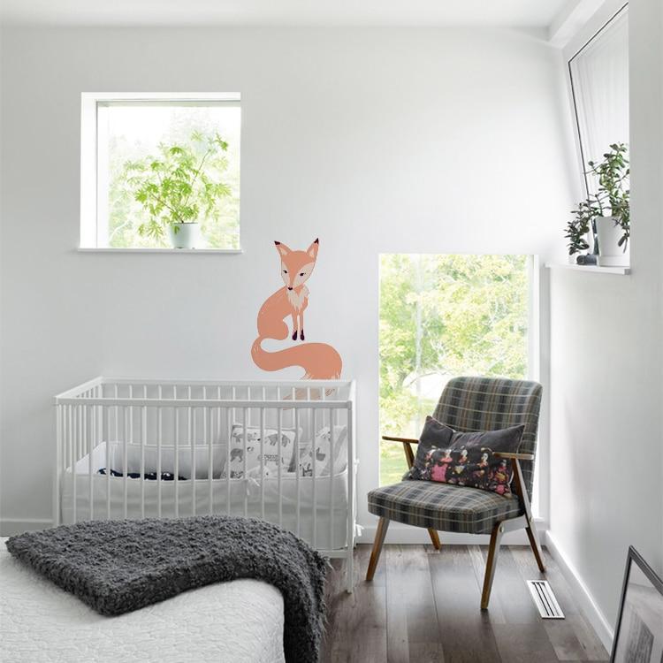 Sticker renard pour enfant au-dessus d'un lit bébé blanc et fauteuil gris