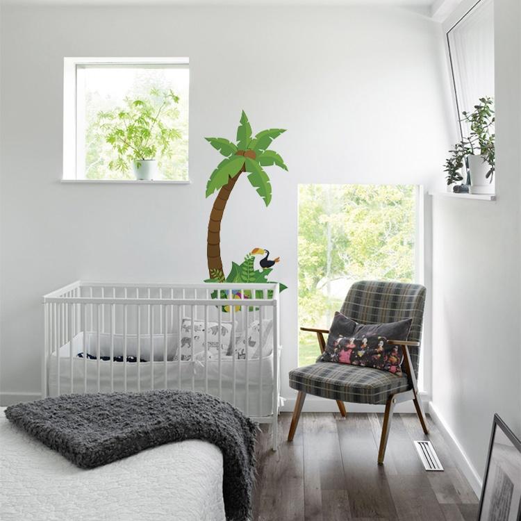 Sticker palmier pour enfant au-dessus d'un lit bébé blanc et fauteuil gris