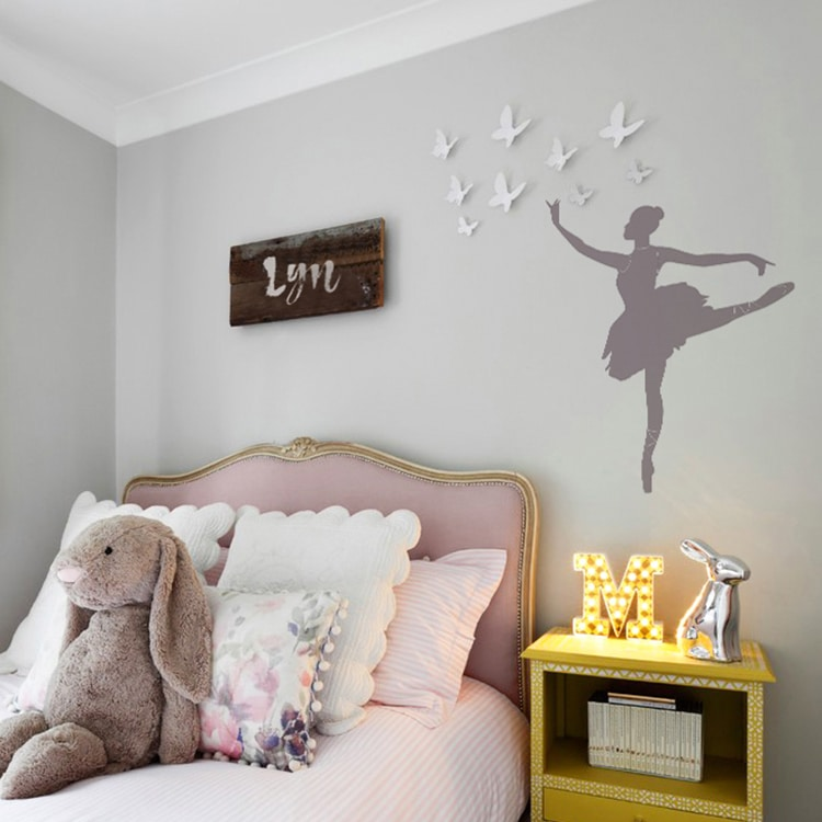 Sticker silhouette danseuse au-dessus d'un lit rose avec coussins clairs