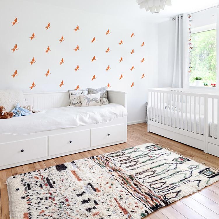 Sticker silhouette fée orange au-dessus d'un lit blanc