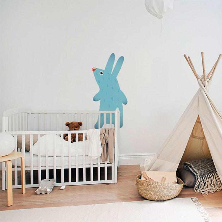 Sticker lapin bleu au-dessus d'un lit bébé blanc et tente