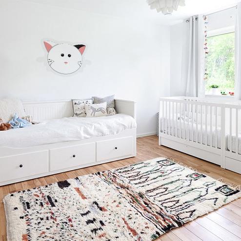 Sticker tete de chat au-dessus d'un lit d'enfant blanc